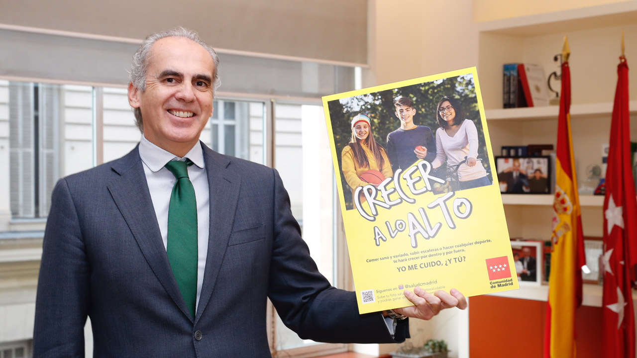Enrique Ruiz Escudero, consejero de Sanidad de Madrid, sujeta el cartel de la campaña.