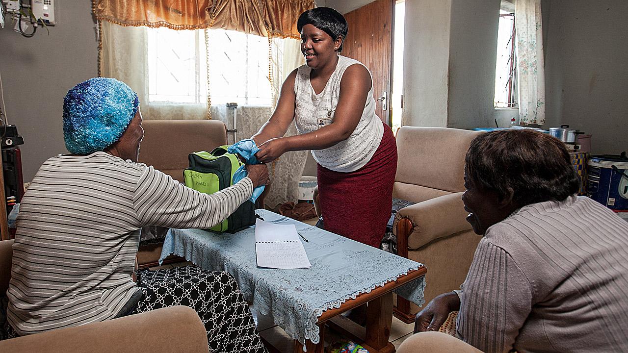 Una cuidadora de la comunidad entrega el tratamiento antirretroviral a una paciente en Sunnydale, Eshowe, KwaZulu-Natal, dentro del programa comunitario de Médicos Sin Fronteras.
